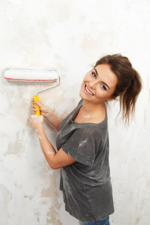 housepainter: Happy beautiful young woman doing wall painting