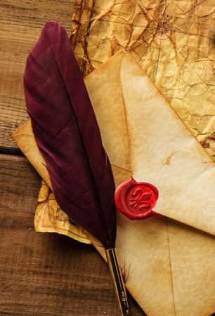 vintage envelope: Envelope and quill pen on vintage paper over wooden  Stock Photo