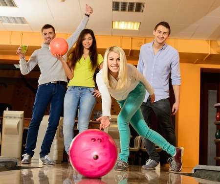 Group of four young smiling people playing bowling  Stock Photo