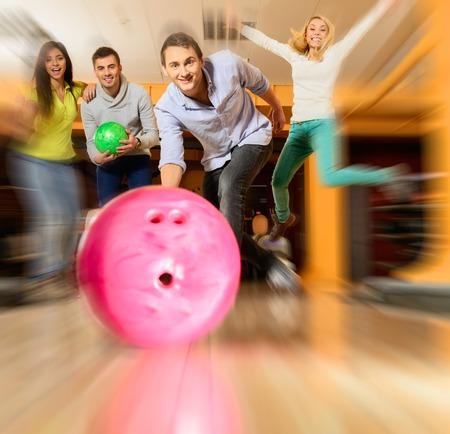 bolos: Grupo de cuatro personas sonrientes jovenes que juegan al bowling Foto de archivo