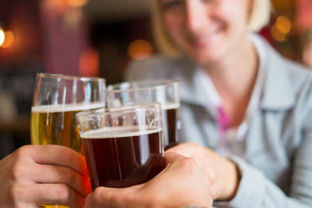cheers: People with beer toasting in a pub