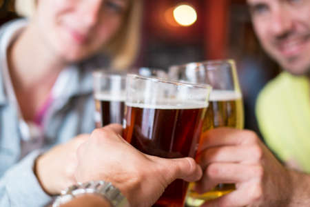 hombre tomando cerveza: Amigos con el tostado de cerveza en un pub