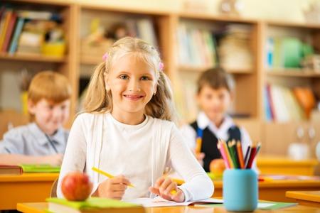 Little schoolgirl sitting behind school desk during lesson in school photo