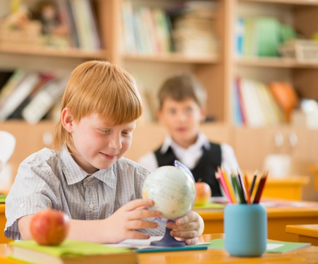 Little redhead schoolboy behind school desk during lesson  photo