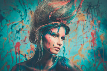 alien face: Young woman muse with creative body art and hairdo