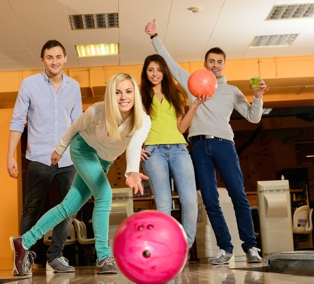 four person: Group of four young smiling people playing bowling  Stock Photo