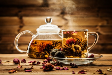 oolong: Teapot and glass cup with blooming tea flower inside against wooden background