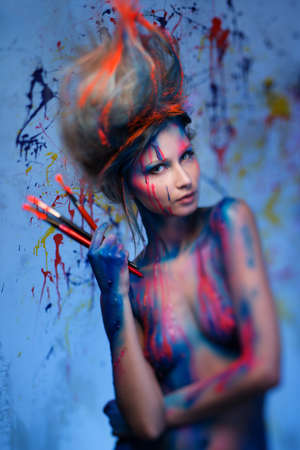 Young woman muse with creative body art and hairdo holding paint brushes  Stock Photo