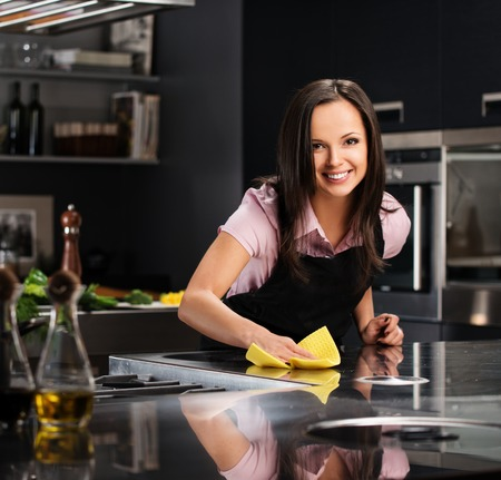 charlady: Young cheerful woman cleaning modern kitchen Stock Photo