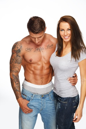Young woman embracing man with bared muscular torso  photo