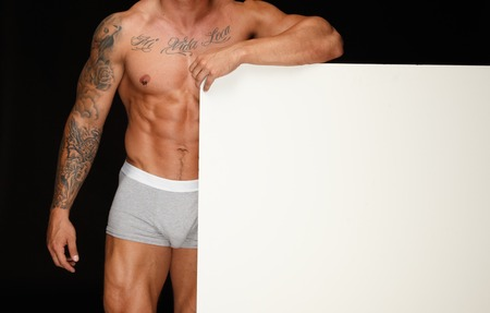 showing muscles: Man with athletic muscular body holding blank notice board