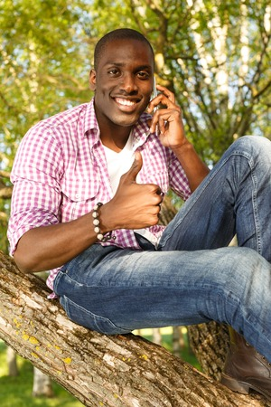 afro american: Young smiling african american sitting on a tree in park with mobile phone Stock Photo