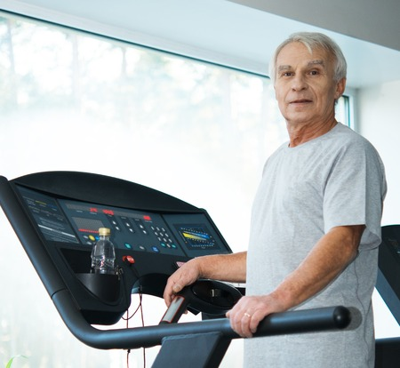 Tired senior man on a treadmill with bottle of water photo