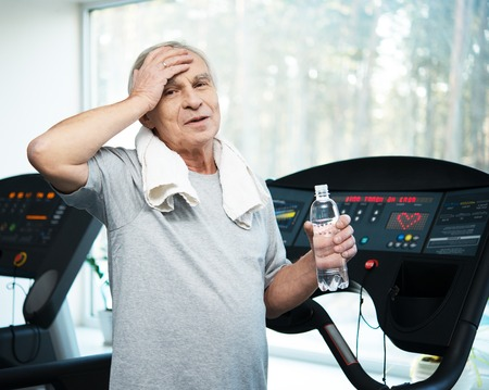 Tired senior man on a treadmill with towel and bottle of water photo