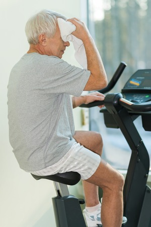 Tired senior man with towel on exercise bike in fitness club photo