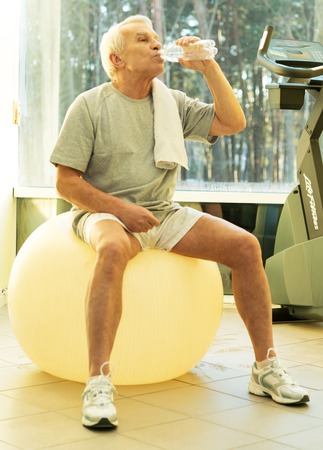 Tired senior man with towel and bottle of water on exercise fitness ball photo