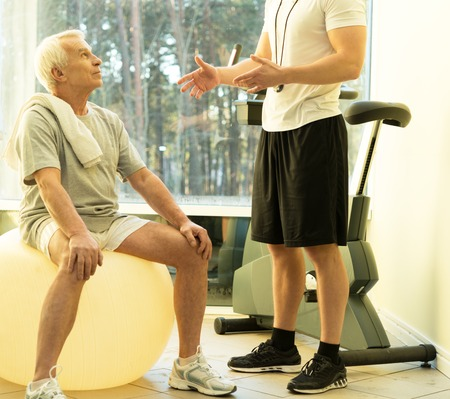 medical personal: Personal trainer explains to a senior man how to do exercise on a fitness ball