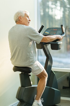 man working out: Senior man doing exercise on a bike in a fitness club