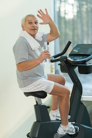 Senior man with bottle of water on a bike in a fitness club photo