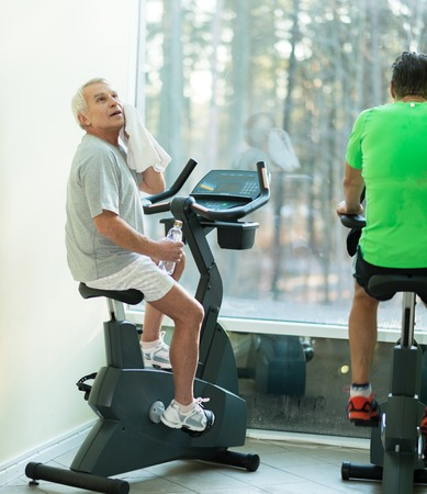 man working out: Tired senior man with towel on exercise bike in fitness club