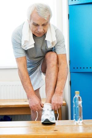 water aerobics: Senior man tying up sneakers in fitness club locker room Stock Photo