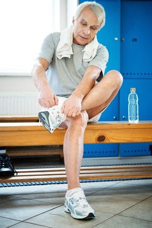aerobic treatment: Senior man tying up sneakers in fitness club locker room Stock Photo