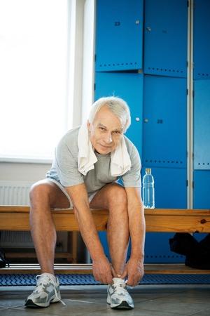 Senior man tying up sneakers in fitness club locker room photo