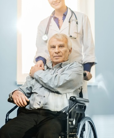 mobility nursing: Cheerful young nurse woman with senior man in wheelchair  Stock Photo