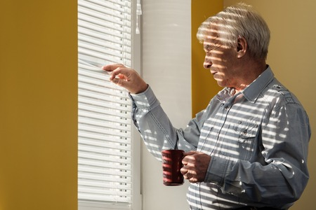 the elderly residence: Senior man with cup looking out the window through jalousie