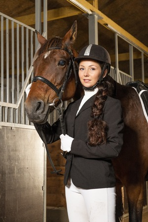 equitation: Beautiful girl with her horse in a stall  Stock Photo