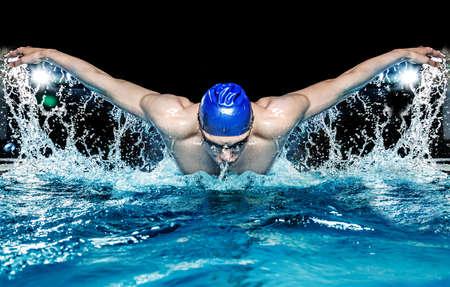 競技会: スイミング プールの青い帽子の筋肉の若い男