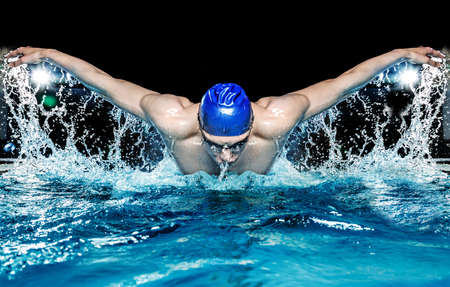 swimming goggles: Muscular young man in blue cap in swimming pool