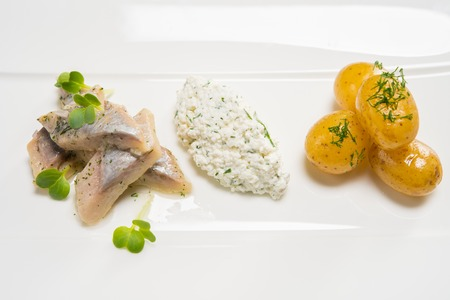 Fish slices with potato on a white plate photo