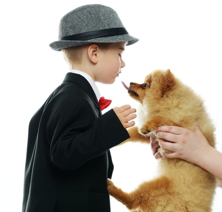 Little boy in hat and black suit with little spitz photo
