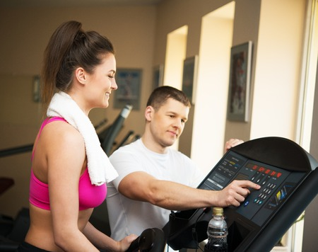 Trainer explains to a young woman how to use treadmill in fitness club photo
