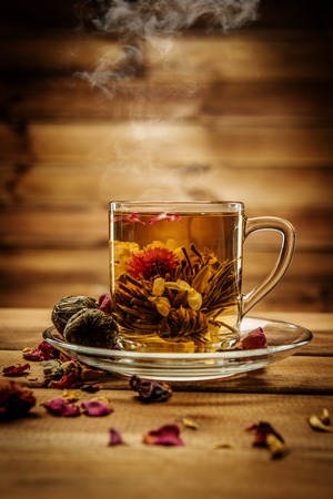 Glass cup with tea flower against wooden background  photo
