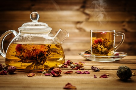 chinese tea pot: Teapot and glass cup with blooming tea flower inside against wooden background