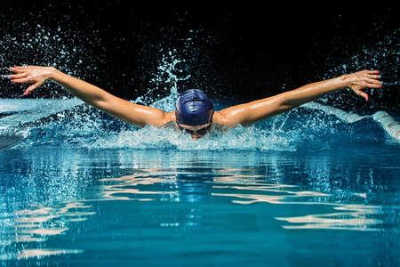 swim?: Mujer joven en la tapa de color azul y traje de baño en la piscina