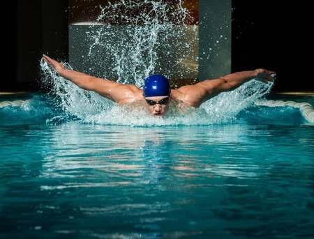 an athlete: Muscular young man in blue cap in swimming pool