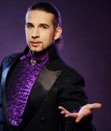 conjuror: Young handsome brunette magician in stage costume  Stock Photo