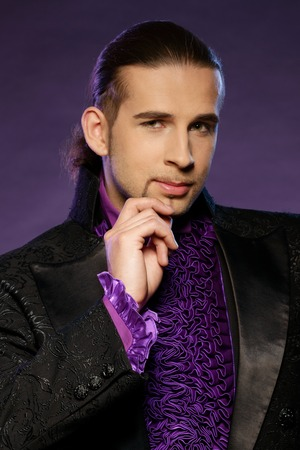 illusionist: Young handsome brunette magician in stage costume  Stock Photo