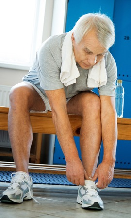 changing clothes: Senior man tying up sneakers in fitness club locker room Stock Photo