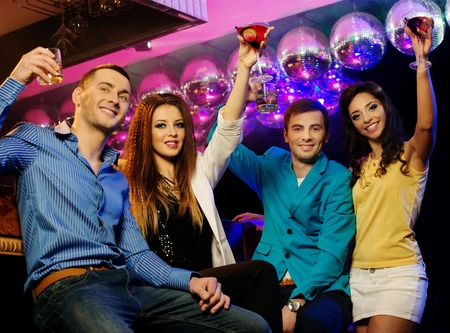 Group of cheerful young friends sitting with drinks at night club photo