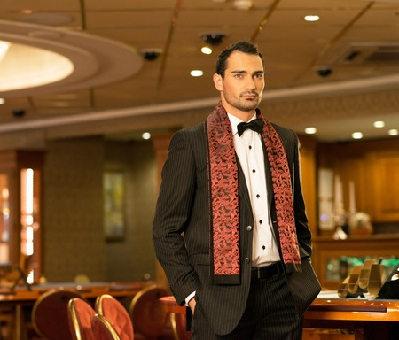 Handsome brunette wearing suit and scarf in luxury interior  photo