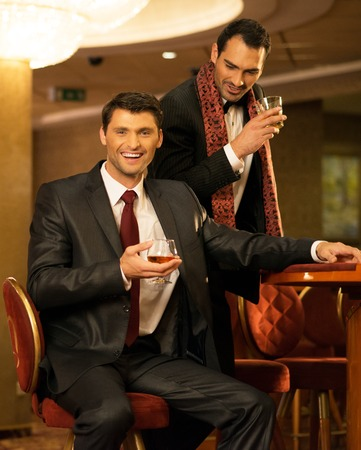 Two young men in suits behind gambling table in a casino photo