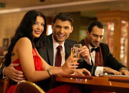 Happy young people behind gambling table with drinks photo