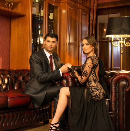 wealthy: Elegant couple in formal dress in luxury cabinet interior Stock Photo