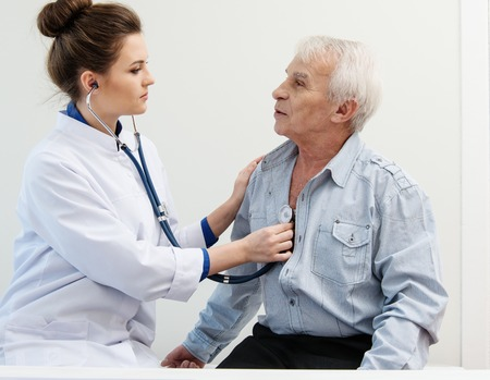 daybed: Senior man and doctor woman with stethoscope Stock Photo