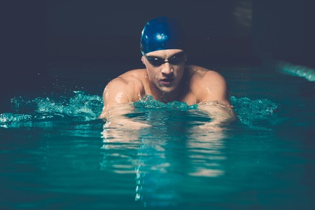 Muscular young man in blue cap in swimming pool photo