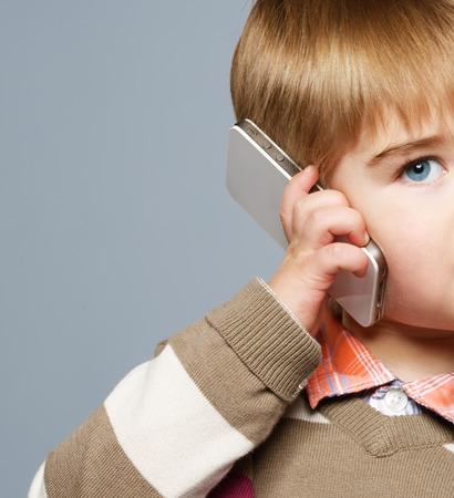 niños platicando: Niño pequeño con el teléfono móvil